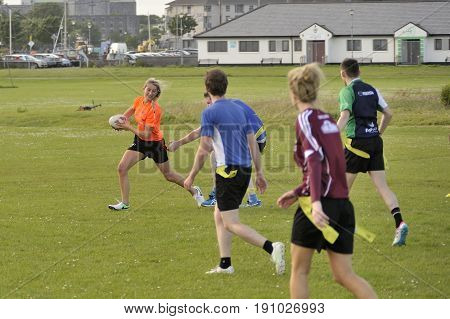 Claddagh Galway Ireland june 2017 friends playing touch rugby in the free public south park fields a girl is running with the ball while a player from the other team almost get her strip.