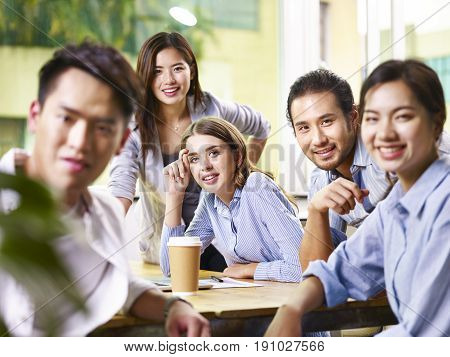 a team of asian and caucasian businesspeople looking at camera smiling during business meeting.