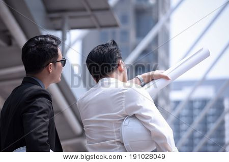 Asian Businessman Discuss With Engineer Architect In Suite, Looking And Point To Finger Forward Away