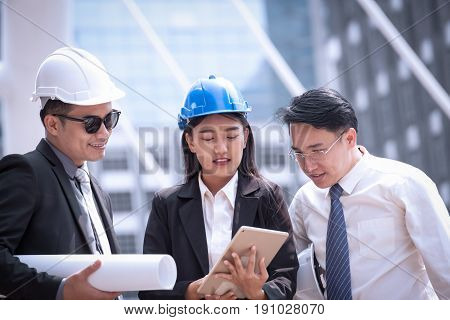 Asian Businessman And Woman Discuss With Engineer Architect Professional Wearing Safety Helmet And S