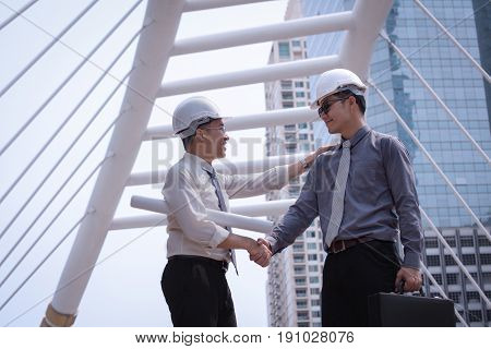 Asian Businessman Discuss And Shake Hand With Engineer Architect Professional Wearing Safety Helmet