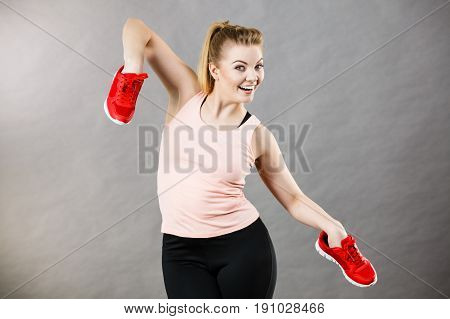 Happy sporty smiling woman presenting sportswear trainers red shoes comfortable footwear perfect for workout and training.