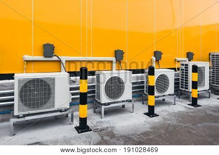 Air Conditioner Compressor Installed Outside Building With Yellow And Black Warning Pole On The Grou