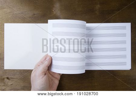 Hand turns over the pages of a notebook on a wooden background