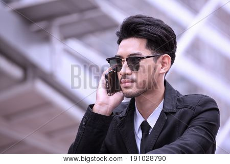 businessman wear sunglasses and using cell phone