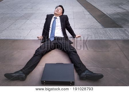 Asian businessman wearing glasses tired and briefcase for working lay down on the floor