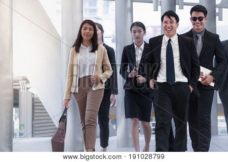 Group of Business People Walking and smiling with colleague on business street background