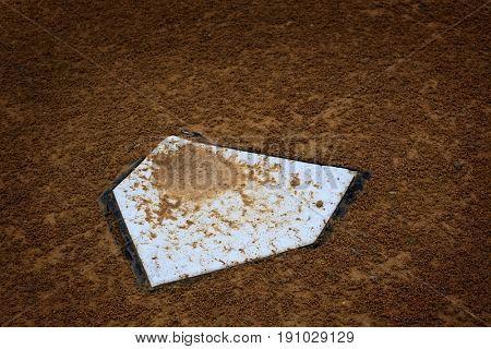Baseball home plate base in rich fresh dirt