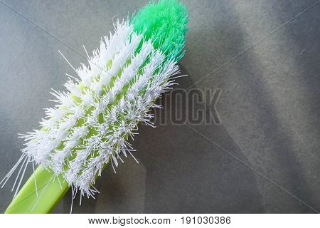 close up texture of green washing brush on the textile floor