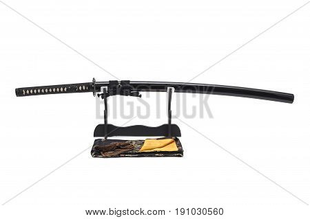 Japanese sword and scabbard on stand white background black silk bag at front.