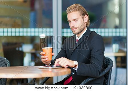 Handsome businessman enjoying a cup of coffee and using his tablet