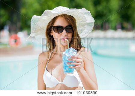 Beautiful woman having a drink at the swimming pool