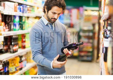 Man in a supermarket choosing a wine