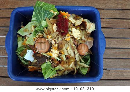 Flat lay view of container full of domestic food waste ready to be composted in the home garden. Food recycling and environment concept. copy space