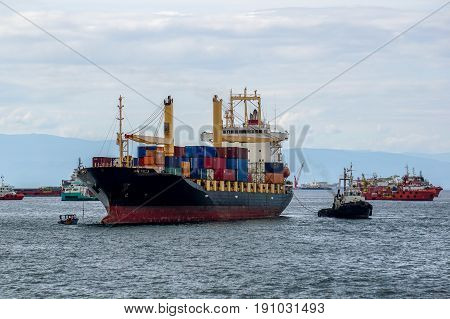 Labuan,Malaysia-July 15,2016:A tugboat maneuvers vessels by pushing or towing the container ship with full of cargo docked in Labuan,Malaysia.The abolishment of cabotage policy is set to benefit this duty free island economically