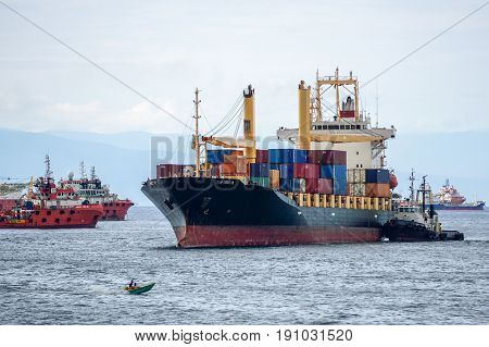 Labuan,Malaysia-July 15,2016:Tug boat towing the container ship with full of cargo docked in Labuan,Malaysia.The abolishment of cabotage policy is set to benefit this duty free island economically