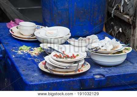 unwashed dish with food garbage and fly at unhealthy unclean dirty restaurant.