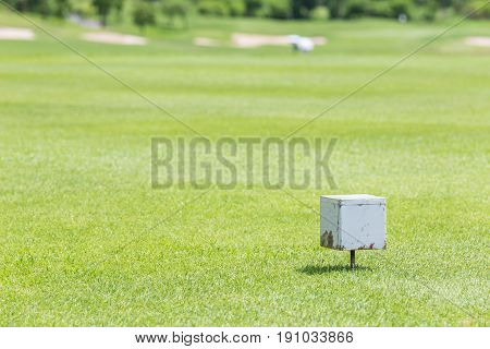Close-up white color wooden tee off area or tee box with blurred natural green golf course in background.