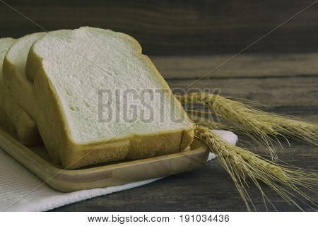 Sliced bread stack on wood plate. Homemade bread for breakfast on rustic wood table. Soft and sticky homemade bread for delicious toast in breakfast. Homemade bakery background with copy space. Delicious soft bread underexposure concept.