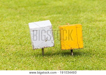 Close-up white and yellow color wooden tee off area or tee box with blurred natural green golf course in background.