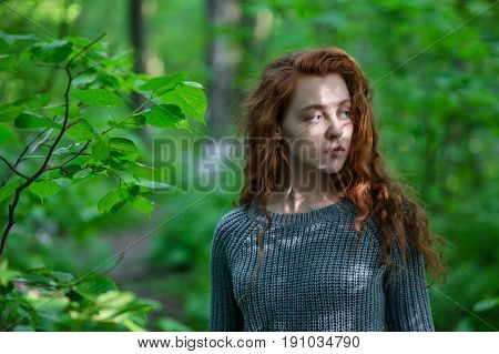 Artistic portrait of young redhead girl in woods