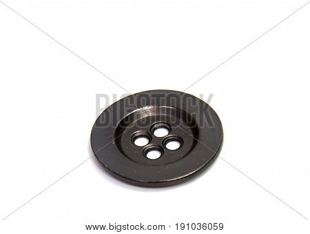 Single clothing button isolated over the brown background