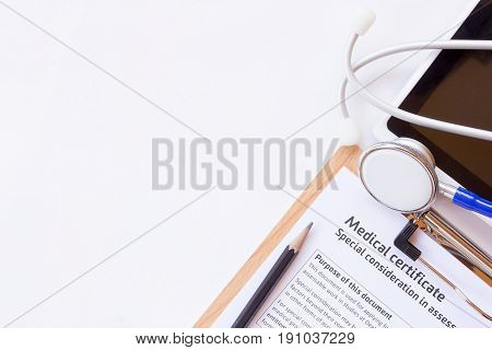 Workplace of a doctor. Medical certificate formsethoscope and smart phone on wooden desk background. Top view with copy space. Healty concept.