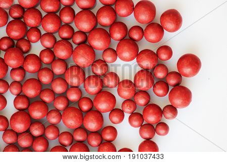 Macro photo of many red ball-shaped pills. Tibetan folk medicine from the herbal complex