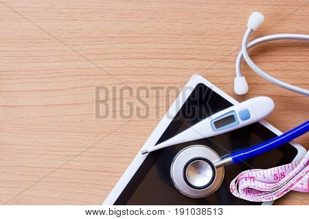 Workplace of a doctor. Stethoscope and smart phone with thermometer on wooden desk background. Top view with copy space. Healty concept.