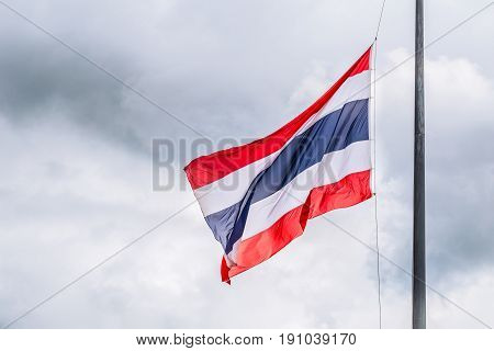 Thai flags half-mast on cloudy storm background.