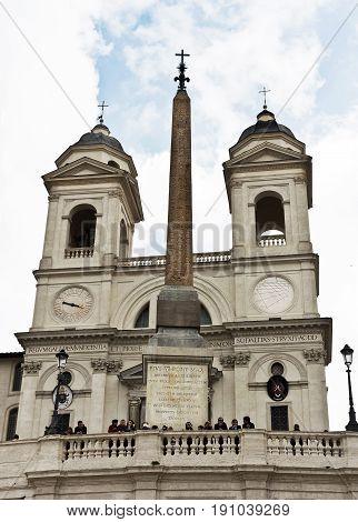 Rome, Italy - April 18, 2017: Trinita dei Monti, also Santissima Trinità al Monte Pincio - titular church (from April 13, 1587) in Rome, on top of the Spanish Steps.An antique obelisk (the Roman imitation of the Egyptian obelisk) from the gardens of Sallu
