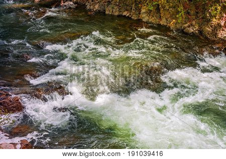 Rapid stream flow along shore covered with stone. beautiful nature background in summer time.