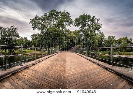 Bridge over pond in Churchill Park in Copenhagen Denmark a cloudy day of summer