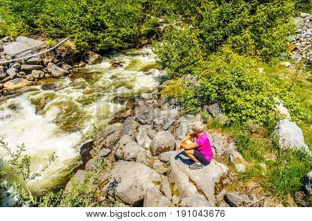 Woman looking at the fast flowing waters of Joffre Creek just before it flows into Lillooet Lake along the Duffy Lake Road, Highway 99, between Pemberton and Lillooet in southern British Columbia
