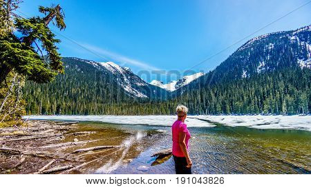 Woman enjoying the view of the partly frozen Lower Joffre Lake and the Matier Glacier in the Coast Mountain Range along the Duffey Lake Road, between Pemberton and Lillooet in southern British Columbia