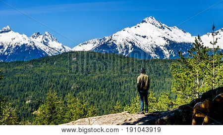 Man looking at the Tantalus Mountain Range with snow covered peaks of Alpha Mountain, Serratus and Tantalus Mountain, seen from a viewpoint along the Sea to Sky Highway between Squamish and Whistler