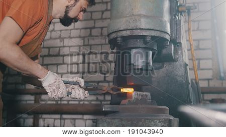 The blacksmith treats the metal part under the hard pressure, metal bends