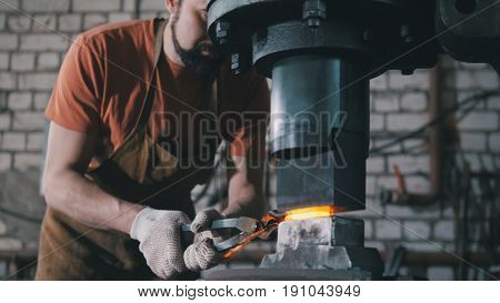 In the workshop of a blacksmith. A man with a beard puts a red-hot forged piece under an automatic hammer