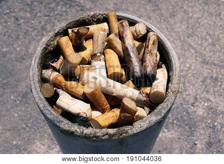 Pile of cigarettes butts over a metal pole during a bright summer day.