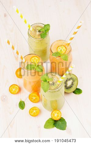 Freshly blended orange kumquat and green kiwi fruit smoothie in glass jars with straw mint leaf cut ripe berry close up. White wooden board background vertical.