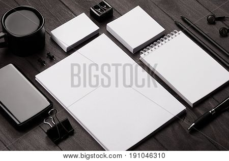 Corporate identity template blank stationery set with coffee and earphone on black stylish wood background. Mock up for branding business presentations and portfolios.