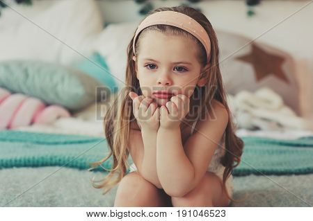 indoor portrait of sad 5 years old child girl sitting on bed