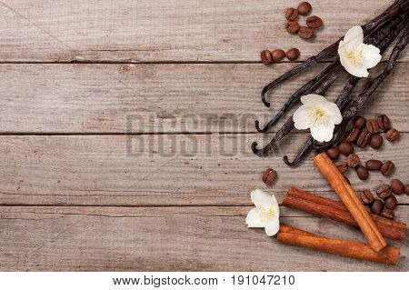 Vanilla sticks with cinnamon and coffee beans on a old wooden background with copy space for your text. Top view.