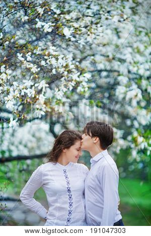 The man gently kisses his wife on the forehead for a walk through the flowering magnolia garden
