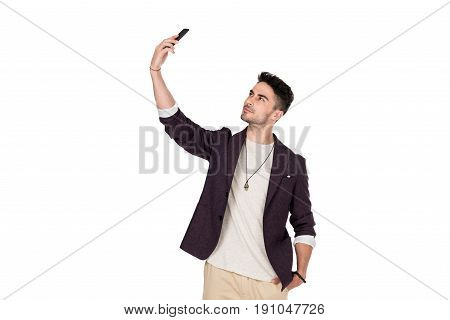 Stylish young man standing with hand in pocket and taking selfie with smartphone