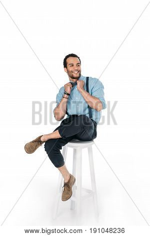 smiling african american man posing while sitting on chair isolated on white