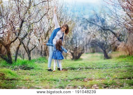 The woman teaches the girl to fly. Mother and daughter stand in the midst of a blooming apricot garden with arms outstretched