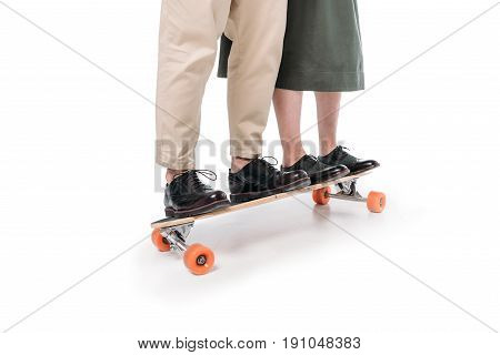 Low Section Of Casual Couple Riding On Skateboard Isolated On White