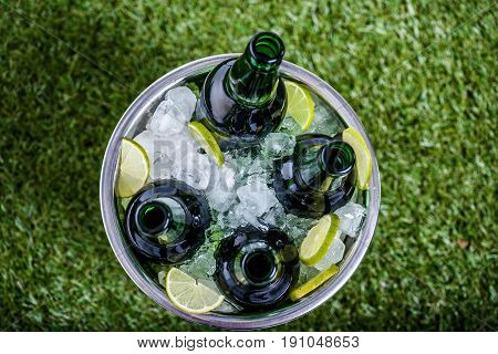Top View Of Bucket With Ice Cubes, Refreshing Beer Bottles And Lemon Pieces On Green Grass