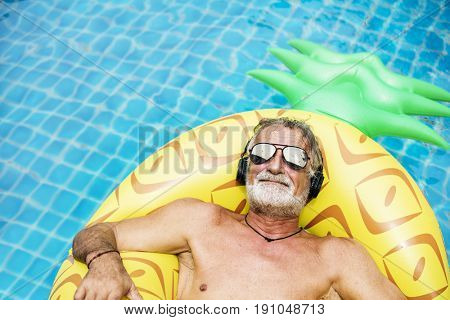 Closeup of caucasian senior man in the pool with headphones